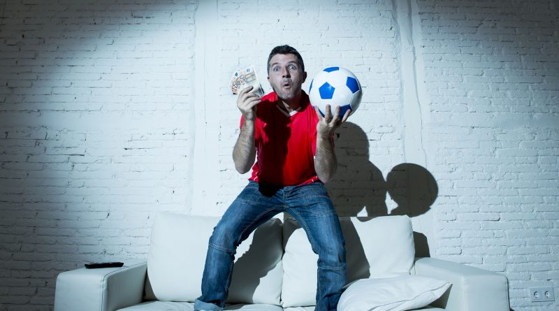 crazy man holding money and soccer ball watching football on tv internet online bet gambling