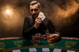 Bearded man showing poker cards on smoke black background